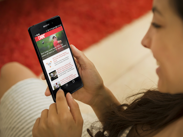 A girl consuming content from Golf News Net app created with Shoutem